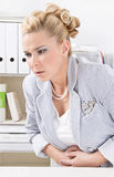 La donna ha dolore mestruale all'ufficio. Fotografia Stock Libera da Diritti
