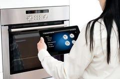 La donna ha installato il programma di cottura del forno Concezione di usando h astuta Fotografie Stock Libere da Diritti