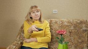 La donna ha invecchiato i canali televisivi telecomandati dei commutatori sullo strato a casa Sta riposando dopo una giornata cam stock footage
