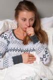 La donna ha la tosse, l'influenza e febbre alta Immagini Stock