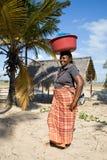 La donna ha merci differenti in una ciotola e la porta sulla sua testa tradizionalmente Fotografie Stock