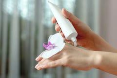 La donna ha messo la crema sulle sue mani, che è fiore dell'orchidea Fotografia Stock Libera da Diritti