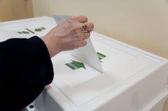 La donna ha messo la scheda elettorale di elezione nella casella fotografia stock