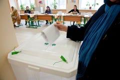 La donna ha messo la scheda elettorale di elezione nella casella Fotografie Stock Libere da Diritti