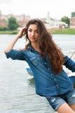 La donna ha peso al fiume sui precedenti eccessivi della città Fotografia Stock Libera da Diritti