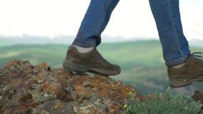 La donna il viaggiatore scala un pendio di montagna con i bastoni per seguire Le gambe si chiudono su Colpo lento stock footage