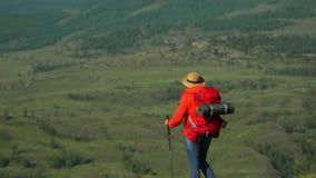 La donna il viaggiatore scala un pendio di montagna con i bastoni per seguire Zaino rosso Bastoni per seguire video d archivio