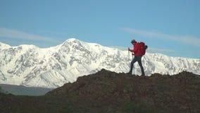 La donna il viaggiatore scala un pendio di montagna con i bastoni per seguire Zaino rosso Bastoni per seguire Rallentatore archivi video