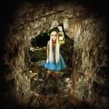 La donna illumina il percorso in una caverna scura Fotografia Stock Libera da Diritti