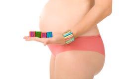 La donna incinta è blocchetti della holding sulla sua pancia Fotografia Stock Libera da Diritti
