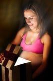 La donna incinta apre il regalo di Natale del contenitore di regalo Fotografia Stock Libera da Diritti