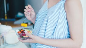 La donna incinta asiatica sta mangiando l'insalata Sembra in buona salute Poiché l'alimento è utile fotografie stock