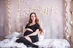 La donna incinta con capelli rossi lunghi, in un vestito nero fotografia stock