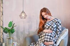 La donna incinta dai capelli rossi si siede in una sedia immagini stock libere da diritti