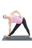 La donna incinta di forma fisica fa la stirata sulla posa di yoga Fotografia Stock