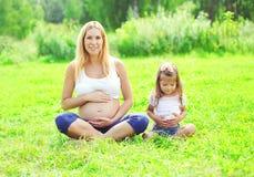 La donna incinta felice, la madre ed il piccolo bambino della figlia sedentesi sull'erba che fa l'yoga si esercitano di estate Fotografia Stock