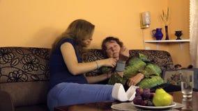 La donna incinta ha messo lo strumento della misura di pressione sanguigna sulla mano della nonna Immagini Stock