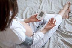 La donna incinta a letto misura la pressione sanguigna, auto-diagnosi, sanità immagine stock libera da diritti