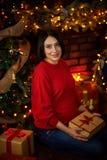 La donna incinta segna la sua pancia all'albero di Natale immagine stock