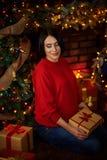 La donna incinta segna la sua pancia all'albero di Natale fotografia stock