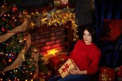 La donna incinta segna la sua pancia all'albero di Natale Immagini Stock