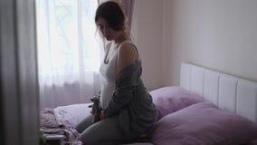 La donna incinta si siede su un grande letto con i cuscini nella camera da letto stock footage