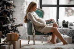 La donna incinta si siede in una poltrona dalla finestra accanto a Christm fotografie stock libere da diritti
