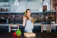 La donna incinta sorridente in cucina sta mangiando il sottaceto Immagine Stock Libera da Diritti