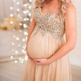 La donna incinta sostiene un grande stomaco con le mani al fondo fotografie stock libere da diritti