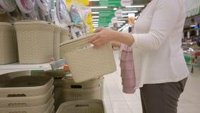La donna incinta sta scegliendo i contenitori di stoccaggio di plastica nel deposito del supermercato stock footage