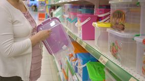 La donna incinta sta scegliendo i contenitori di stoccaggio di plastica nel deposito del supermercato archivi video