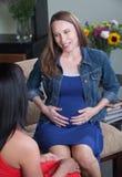 La donna incinta tocca il suo stomaco immagine stock