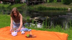 La donna incinta vicino all'acqua di fiume ed alla carta del popolare spedisce Fotografie Stock
