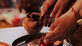 La donna indù mette i petali rossi sul piatto bronzeo video d archivio