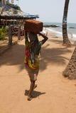 La donna indiana nelle pietre dei sari per la costruzione sulla testa su una spiaggia Goa dell'India Fotografia Stock