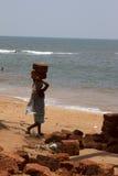 La donna indiana nelle pietre dei sari per la costruzione sulla testa su una spiaggia Goa dell'India Immagine Stock Libera da Diritti