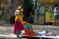 La donna indiana in sari variopinti vende i ricordi, i braccialetti ed i gioielli economici Fotografia Stock
