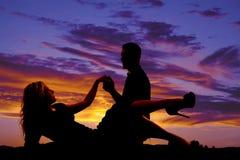 La donna indica la siluetta con l'uomo si tiene per mano Fotografia Stock