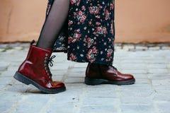 La donna indossa gli stivali rosso scuro della caviglia, calze scure e un vestito lungo fiorito, fotografato al ginocchio fotografie stock