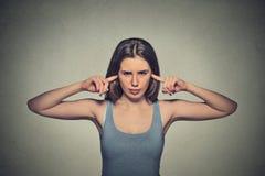 La donna infelice arrabbiata con le orecchie chiuse che vi esaminano si è infastidita Immagini Stock