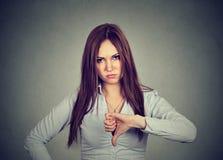 La donna infelice che dà i pollici giù gesture lo sguardo con l'espressione negativa immagine stock libera da diritti
