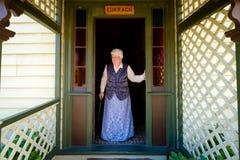 La donna inglese anziana pensionata sta fuori della sua porta immagini stock libere da diritti
