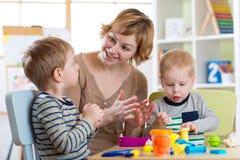 La donna insegna ai bambini che modellano il plasticine nell'asilo Fotografia Stock Libera da Diritti
