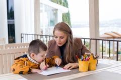 La donna insegna al ragazzo a disegnare con le matite colorate Fotografia Stock