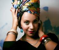 La donna intelligente con creativo compone, scialle sulla testa immagine stock
