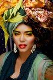 La donna intelligente di bellezza con creativo compone, molti scialli sulla testa come cubian, primo piano di sguardo di ethno immagini stock