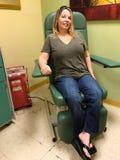 La donna invecchiata mezzo si siede in un tiraggio aspettante del sangue della sedia fotografie stock