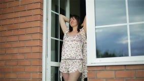 La donna invecchiata mezzo svegliata castana felice in pigiami si apre su un balcone attraverso la porta di vetro stock footage