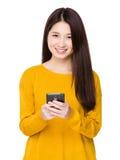La donna invia il messaggio tramite telefono cellulare fotografie stock