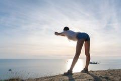 La donna irriconoscibile in blusa e denim leggeri mette l'allungamento in cortocircuito sulla collina con la vista laterale di vi Fotografie Stock